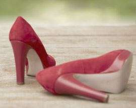 Red high heels laying on wooden ground